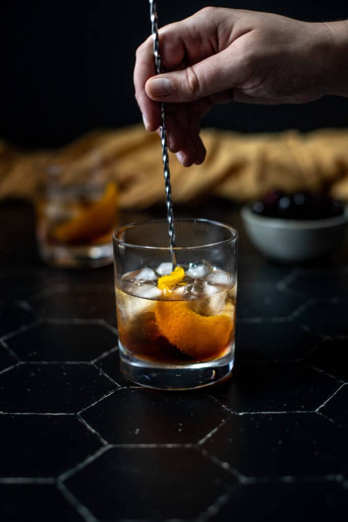 a maple old fashioned on a black tile background, a hand is stirring the cocktail with a bar spoon