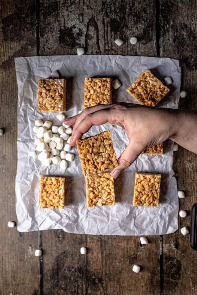 overhead view of peanut butter rice krispie treats with a hand holding one of them