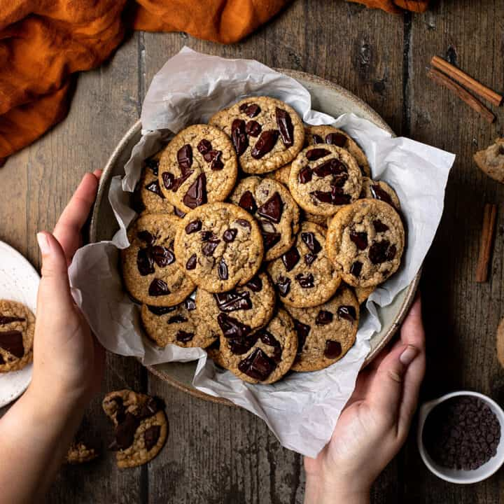 an overhead view of two hands holding a bowl of pumpkin spice chocolate chip cookies