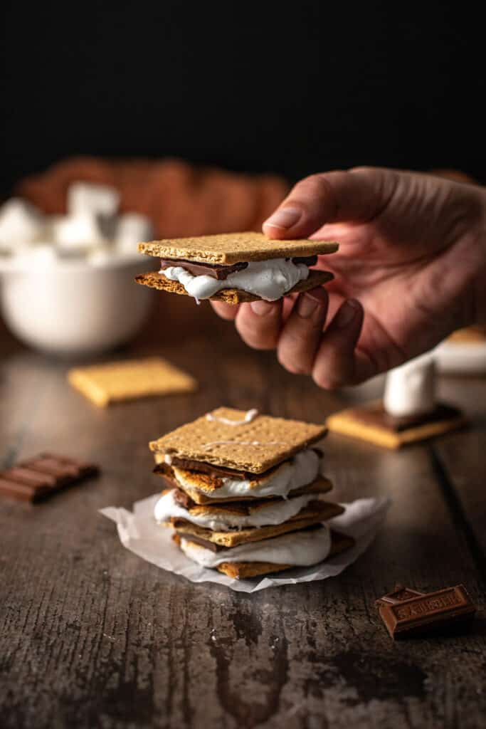 a stack of s'mores, with a hand holding one