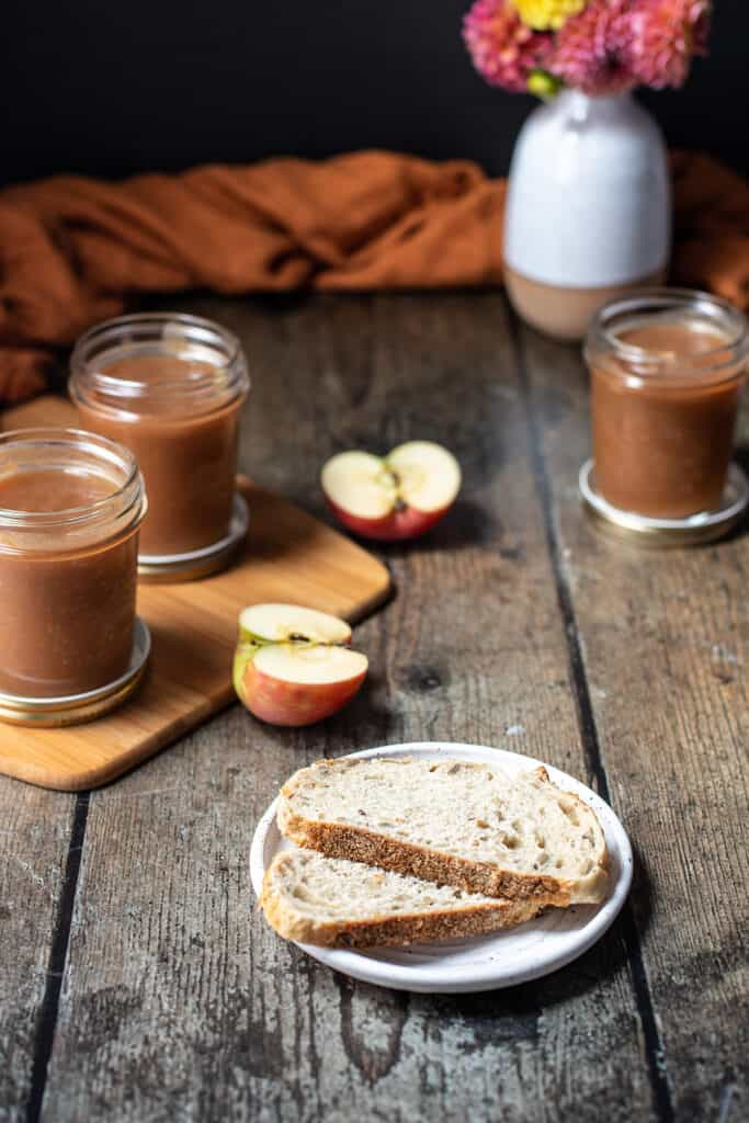 slices of bread in the foreground, jars of apple butter in the background
