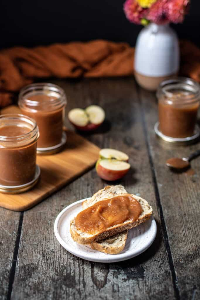 slices of bread with apple butter in the foreground, jars of apple butter in the background
